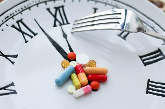 Hodiny, na ktorých sú tabletky a vidlička
