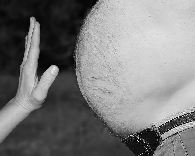 Mužské veľké brucho, pred ktorým je ženská ruka