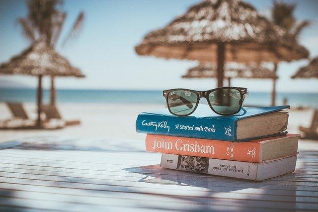Kôpka kníh s okuliarmi na terase, ktorá je na pláži, v pozadí je slnečník.jpg