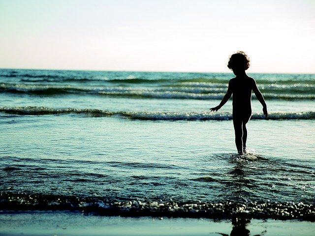 Silueta malého dieťaťa, ktoré kráča do mora.jpg